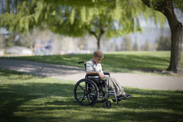 Young boy sitting in a wheelchair at the park.