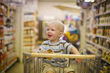 Male toddler sitting in a shopping cart looking delighted