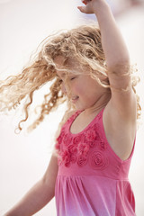 Young girl with curly blonde hair twirls around as she dances while posing for a portrait.