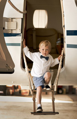 A young boy stepping out of an airplane