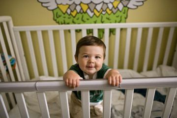 Happy baby boy standing in his crib.