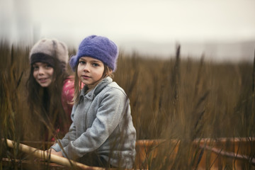 Two young sisters sit together in a wooden canoe among reeds on a lakeshore as they pose for a portrait.