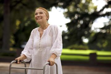 Elderly woman using a walker outdoors.