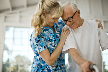Happy young nurse comforting a senior man.
