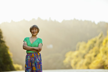 Portrait of a smiling senior woman standing at a lake with her arms crossed.