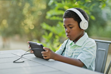 Young boy listening through headphones while using a digital tablet.
