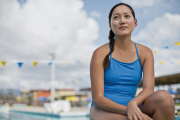 Young woman sitting poolside in her swimsuit.