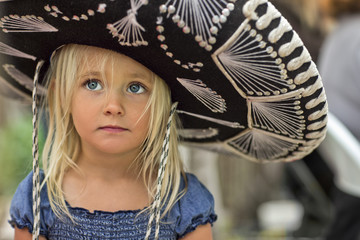 Girl in sombrero standing outdoors