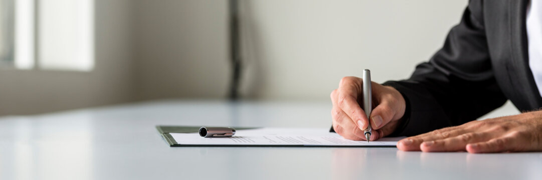 Wide panorama view of businessman hand signing legal or insurance document