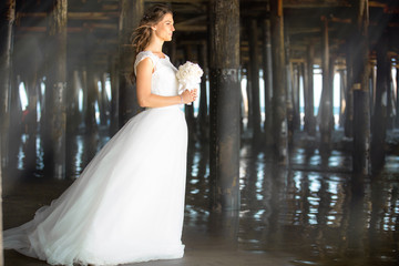 Bride in white dress standing elegant, classic, traditional, glamorous, next to pier pillars