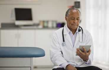 Contemplative male doctor using a digital tablet while sitting inside his office.