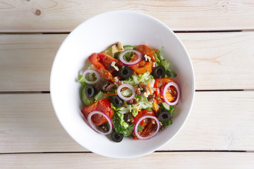 Salad with fried tomato, walnuts, cucumber, onion and olives