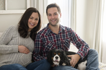 Mid adult couple sitting on sofa with puppy