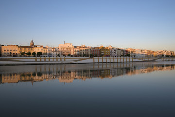 Spain, Seville, Colorful residential building reflecting in Guadalquivir river