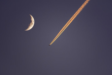 Plane flying next to moon at dusk