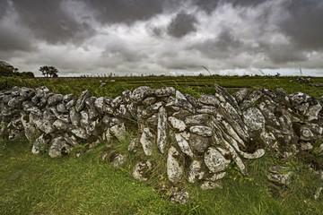 Ireland, County Clare, Burren, Stone wall against stormy sky