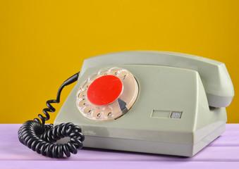 Retro telephone on yellow pastel background.