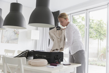 Mature woman packing suitcase at table