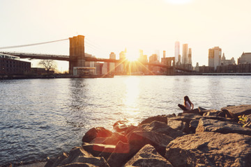 Blurred of a girl sitting on rocks with the view of Brooklyn Bridge and Manhattan skyline at sunset in vintage colour