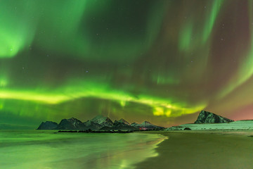 Aurora Borealis reflected in the sea on Myrland beach, Lofoten, Norway