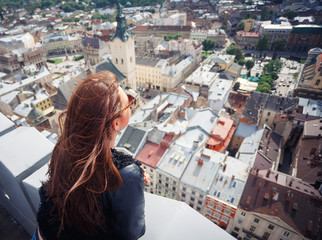 Back view of young woman enjoying Lviv city. Young girl tourist looking at a panoramic view of the city Lviv. Ukraine
