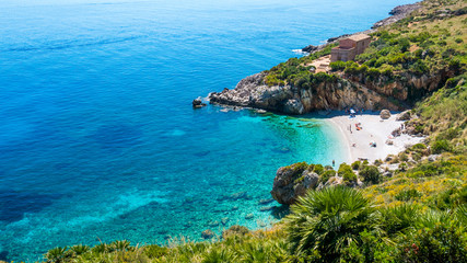 "The paradise beach in Italy: perfect turquoise transparent water, white pebbles surrounded by green. Cove named ""Cala Tonnarella dell'Uzzo"", Natural reserve ""dello Zingaro"", San Vito lo Capo, Sicily."