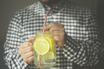 a man drinking fresh drink home made lemonade froma jar mug
