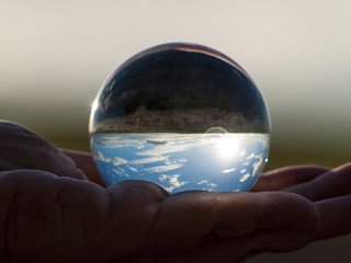 Woman hand holding glass ball with panoramic view of countryside and sky/ Concept for environment