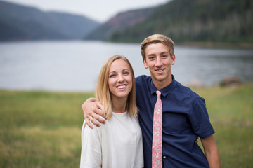 Happy siblings together in front of lake scenery
