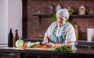 Senior woman chopping fresh vegetables for salad
