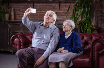 Senior couple taking selfie with smart phone while sitting on couch