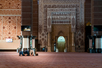 Group of Religious muslim man praying inside the mosque. Islamic praying, prostrating on the ground.