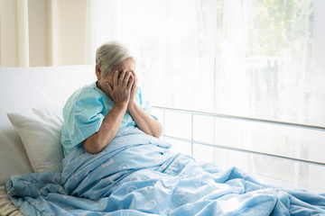 Asian depressed elderly woman patients lying on bed looking out the window in hospital. Elderly woman patients is glad recovered from the illness.