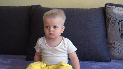 Toddler boy sitting on the couch, blond, blue eyes, watching TV.