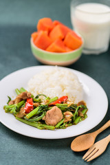 Thai food, stir fried morning glory (Pad Pak Boong) with cooked rice on dish, glass of milk and piece of ripe papaya