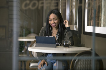 Window view of a black female wearing headphones and watching videos on a tablet in a coffeeshop streaming via 4g or 5g wifi internet.  She is sitting and holding a cup of coffee