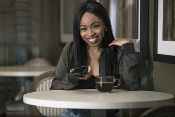 Window view of a black female using a mobile cellphone in a coffeeshop or sidewalk cafe.  She is sitting and having coffee while holding a smart phone.