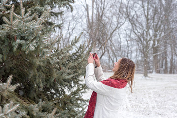 happy woman taking picture of snow falling on pine tree with smart phone