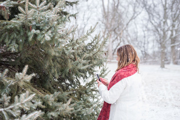 woman taking photo of fresh snow on pine tree branch with smartphone outside in winter
