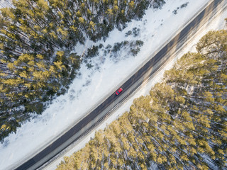 Snowy road with a red moving car in winter. Aerial photography
