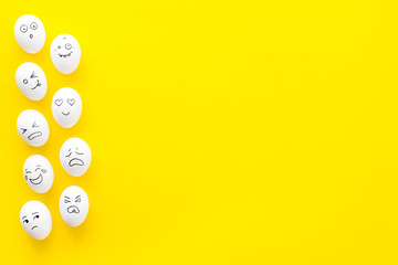 Basic emotions concept. Faces drawn on eggs. Happy, smile, sad, angry, in love. Yellow background top view copy space