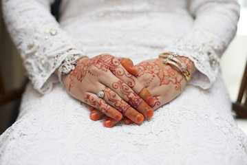 bridal hand with henna paintings and gold bracelets