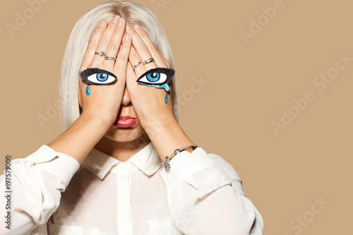 sad woman weeping girl with eyes and tears painted on her hands