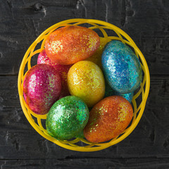 Basket with colorful eggs on a black table. The view from the top.
