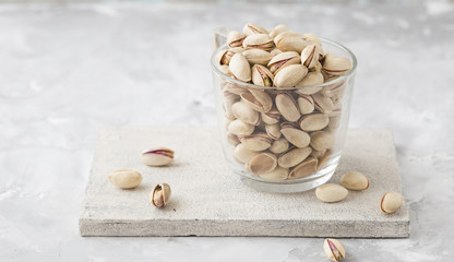 Pistachio in glass. Nuts. Green fresh pistachios as texture. Roasted salted pistachio nuts healthy delicious food studio photo.