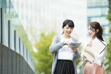 会話しながらタブレットを操作する女性社員たち