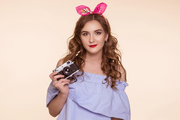 A beautiful young girl in a pin-up image takes pictures on an old DSLR, on a beige background. Metal camera.