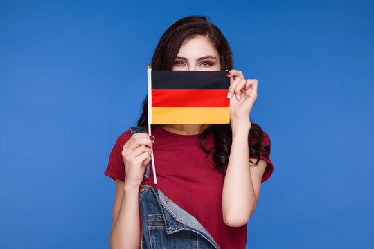 Beautiful brunette woman holding a flag of germany in her hands and covering her mouth, on a blue background. Learning German. Travels. Censorship.