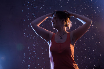 Woman in a yellow t-shirt in a dark Studio illuminated by colored spotlights and drops background