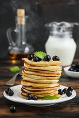 Stack of sweet pancakes with fresh berries and mint on white plate on wooden rustic table